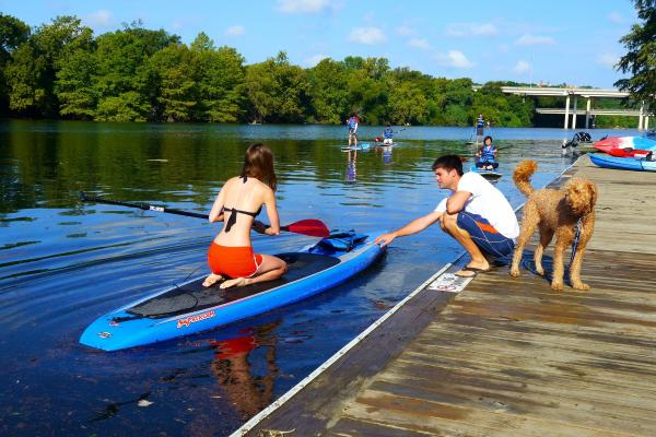 Paddle-boarder launches from the dock on Lady Bird Lake