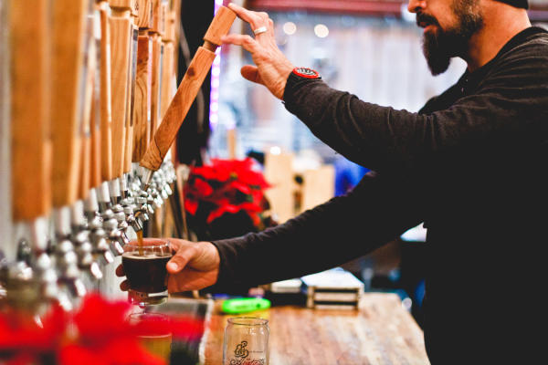 Man pours a pint at Strange Land Brewery