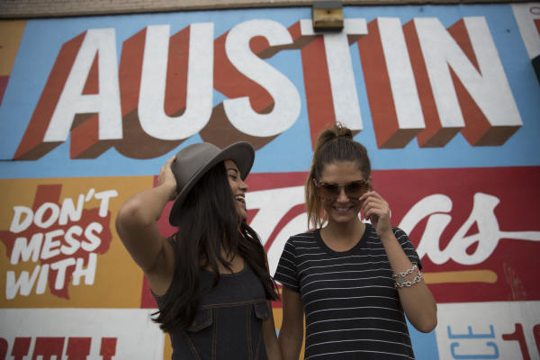Two girls laughing in front of Austin mural