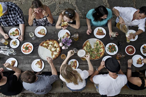 people dining with pizza and beer at large table