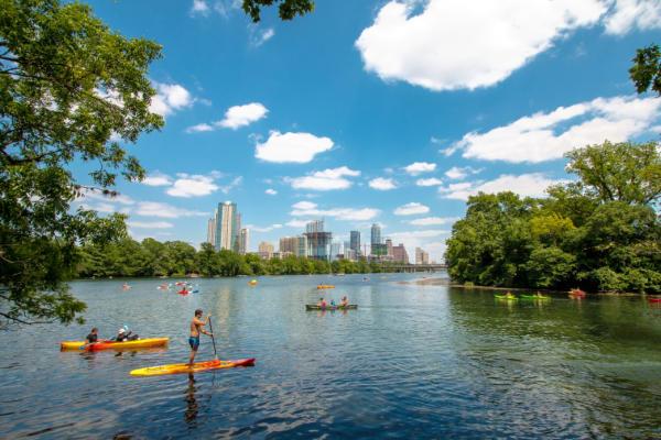 People kayaking and paddle boarding on lady bird lake near downtown Austin Texas