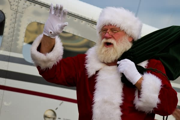 Santa waving in front of Cessna aircraft