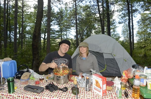 Couple making food while camping
