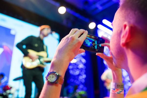 Man takes photo of band on stage at SXSW Music Festival
