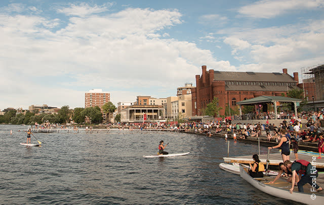 Kayakers paddle in front of a packed Memorial Union Terrace