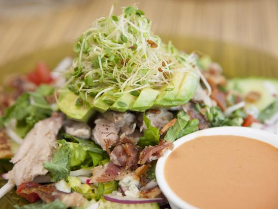 House Salad with dressing topped with avocado + sprouts | credit olivejuicestudios.com