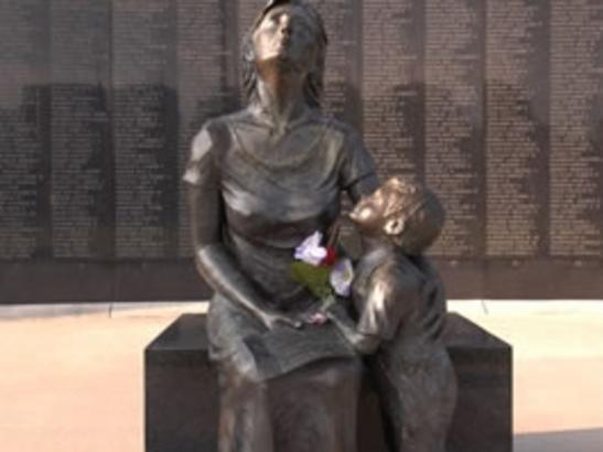 Mother and Son statue sits before the wall | credit olivejuicestudios.com