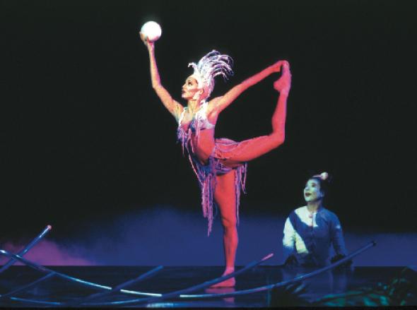 acróbata del Cirque du Soleil sosteniendo una pelota