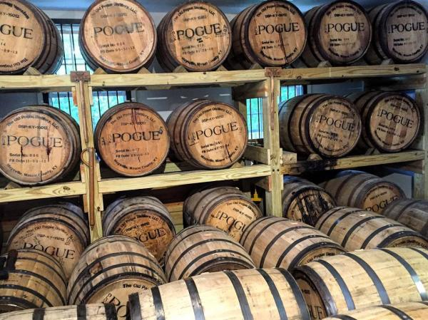 Racks of bourbon barrels in a rickhouse, marked with the name of Old Pogue Distillery