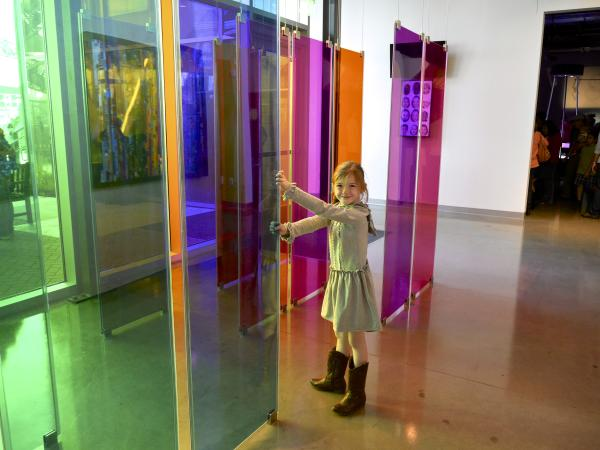 Child playing with color panels at the Thinkery