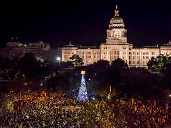 People gathering at the holiday tree lighting in front of the state capitol at night
