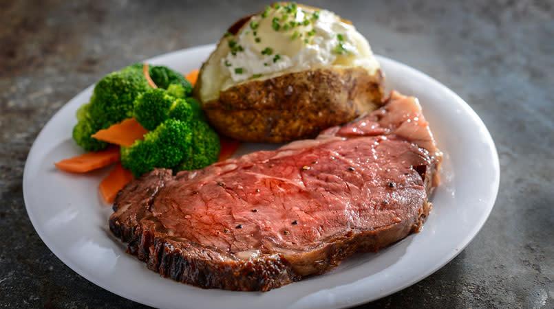 Steak, a baked potato and veggies