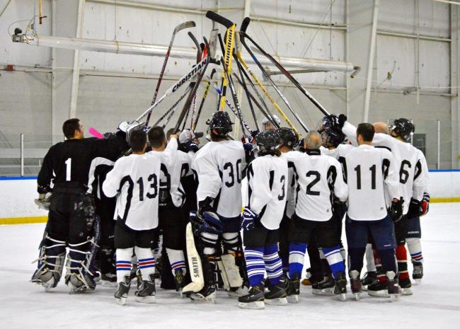 hockey players raise sticks in the air at the Rochester Bill Gray's Ice Plex