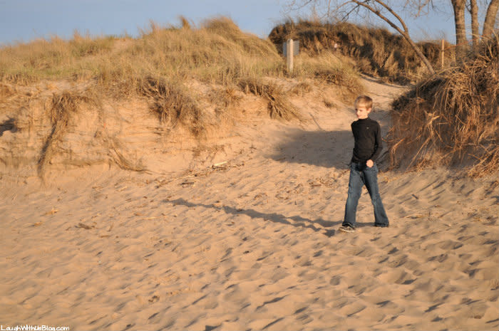 Boy in jeans walking on the Indiana Dunes West Beach sand