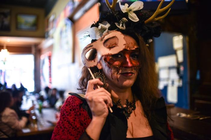 A woman in costume holding a mask