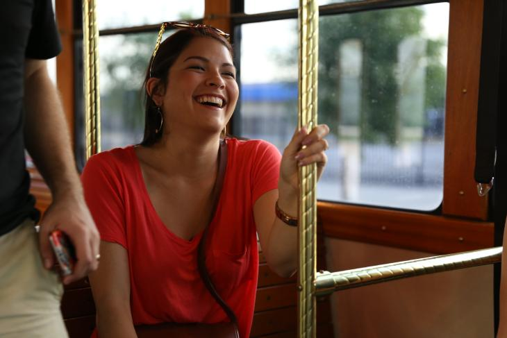 Woman rides free Q-Line Trolley in Wichita KS with a smile on her face