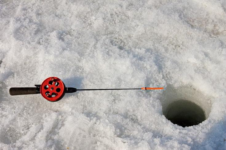 Photo of ice fishing hole with rod next to it on the ice