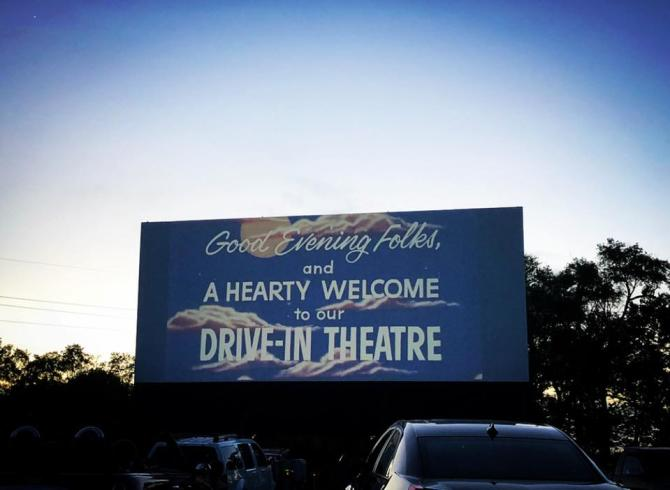 Crowds watch opening credits and welcome message from Starlite Drive-In