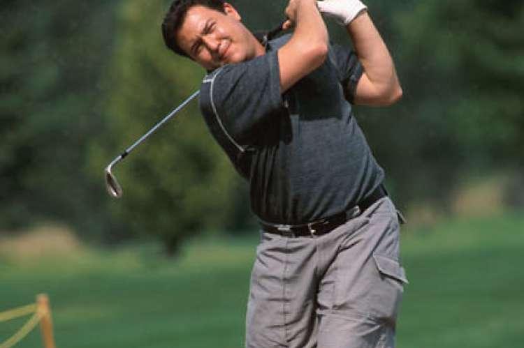 Man Swinging at Golf Ball