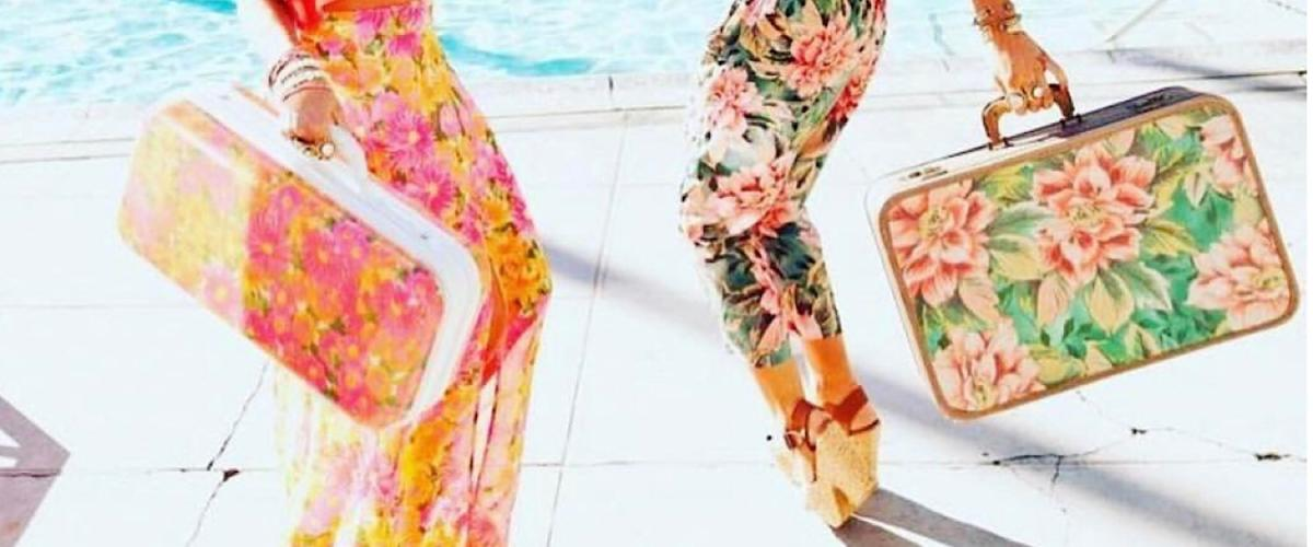 Image of two women's legs in colorful, floral pants carrying matching floral luggage.  They are standing next to a pool and look to be dancing.