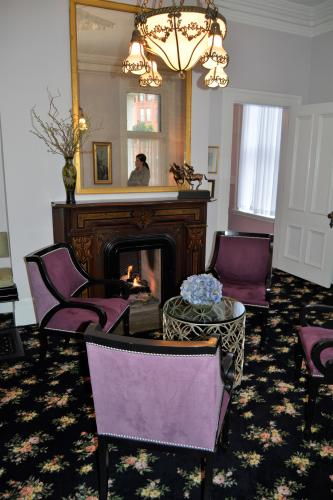 Saratoga Arms sitting room with mauve chairs and fire in fireplace