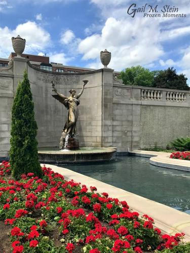 Spirit of Life surrounded by red geraniums in Congress Park