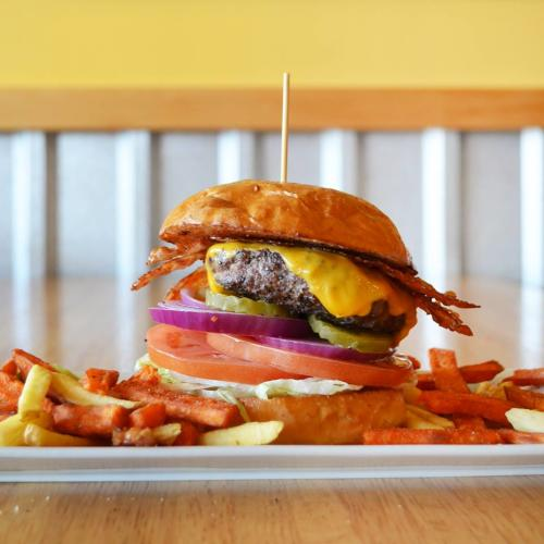 Juicy Burgers & More plate with giant bacon cheeseburger and fries