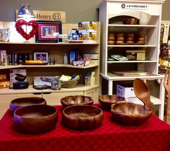 Compliments to the Chef table with display of wooden bowls for sale with additional merchandise behind