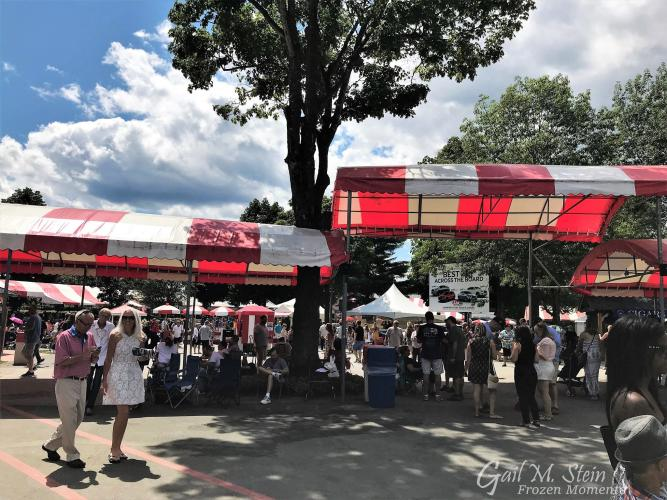 Crowd of people walking under red and white awnings at the track.
