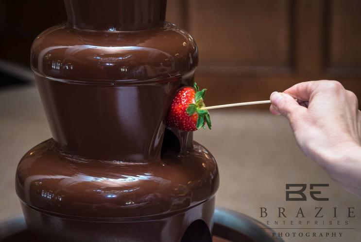 Strawberry on a stick being dipped into a multi-tiered chocolate fountain.