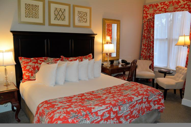 Bedroom with red comforter and white pillows