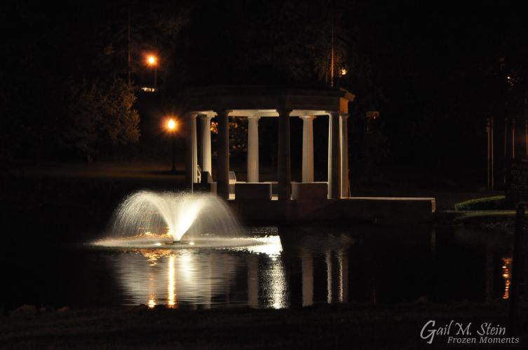 War Memorial and fountain in pond lit up at night