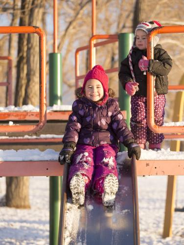 Girls playing on a snowy slide