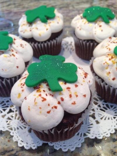 Guinness flavored cupcake with white icing and a green shamrock on top from Our Cupcakery.