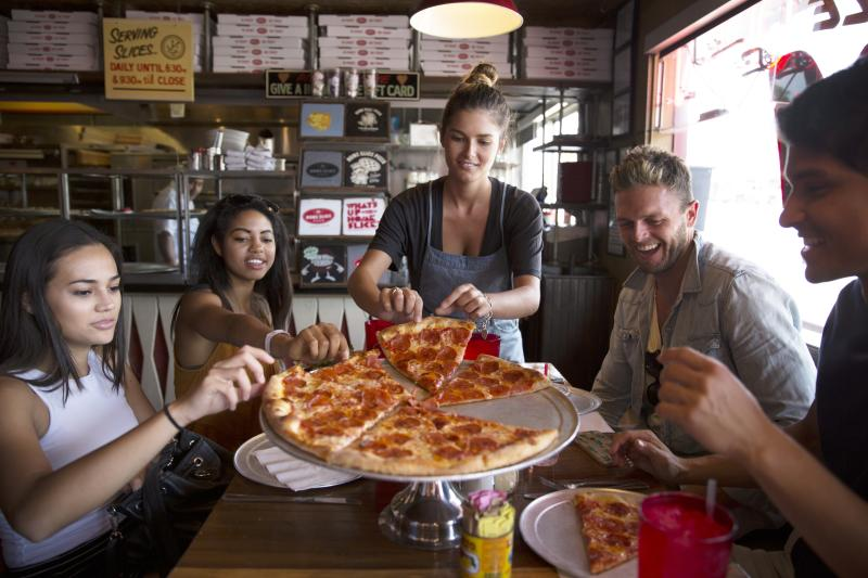 A group enjoying pepperoni pizza at Home Slice