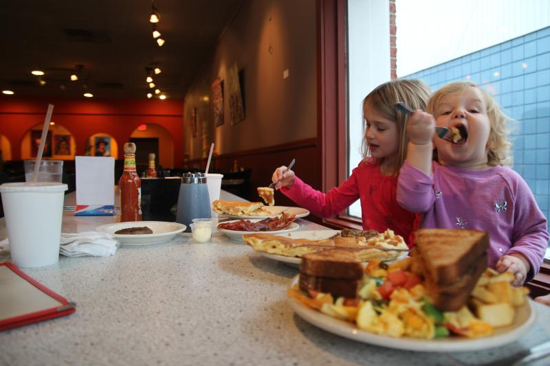 Two young girls eating pancakes at Village Deli