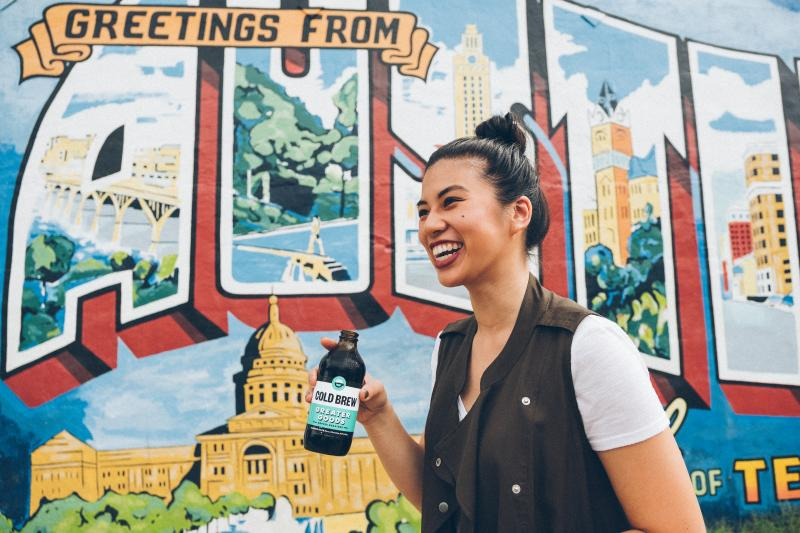 woman with bottled cold brew in front of Austin mural
