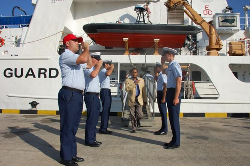 Coast Guard members saluting next to USS Diligence
