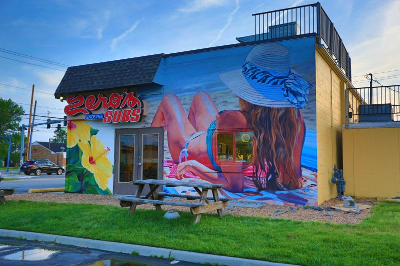 Artist Eric Lindberg of TALENT MuralsVirginia Beach, VAWomen reclining on the beach. The property owner and artist worked together on ideas that kept with the beachy vibe of the other murals at the restaurant. The artist used his hyper realism style on a women reclining at the beach and inserted tropical hibiscus flowers on the left side of the building.
