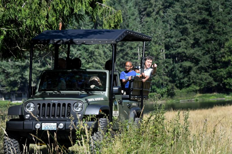 Group riding in Jeep and pointing at animals out of screen