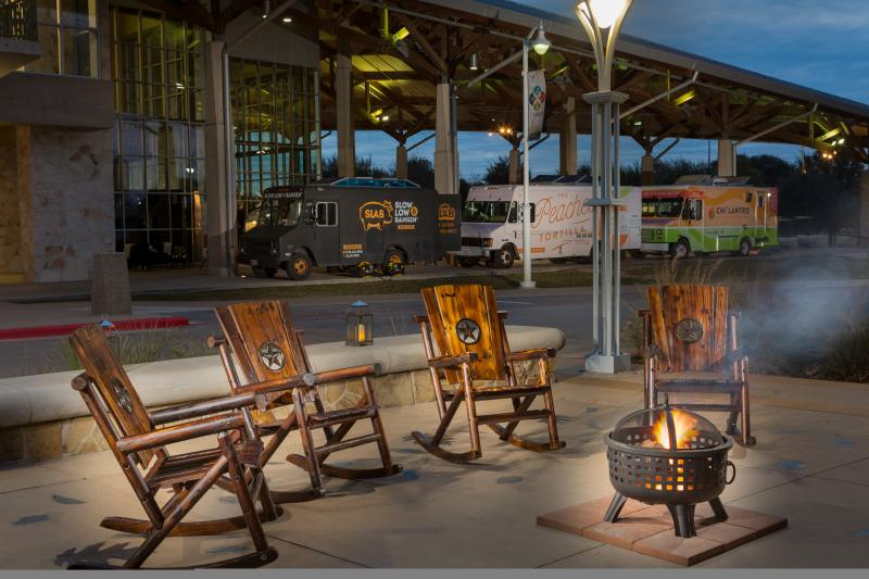 Food Trucks parked outside of Palmer Events Center in Austin Texas with rocking chairs and fire pit in foreground