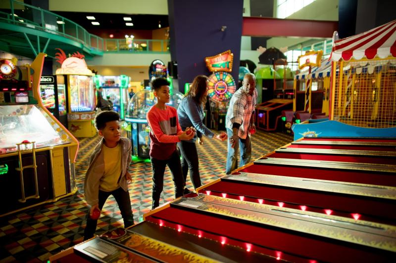 family of four playing skeeball at family fun center