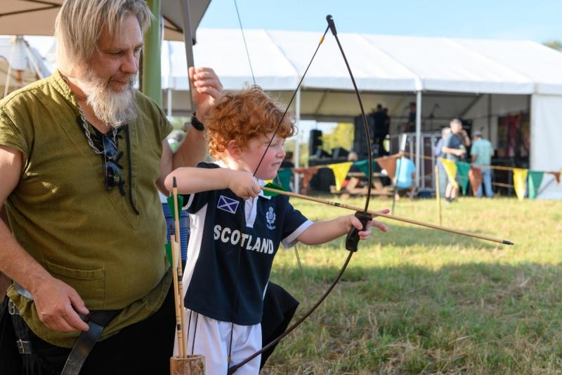 Child practicing with bow and arrow at Austin Celtic Festival in austin texas