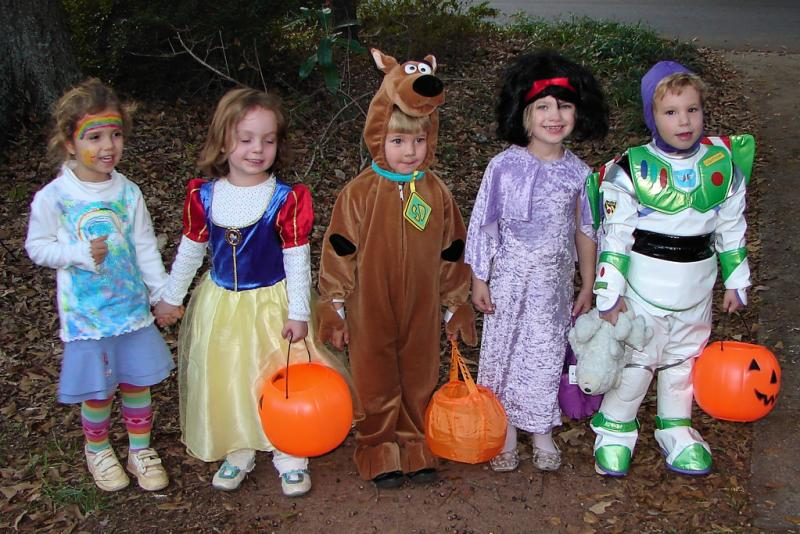 Five children lined up in costumes with trick or treat buckets
