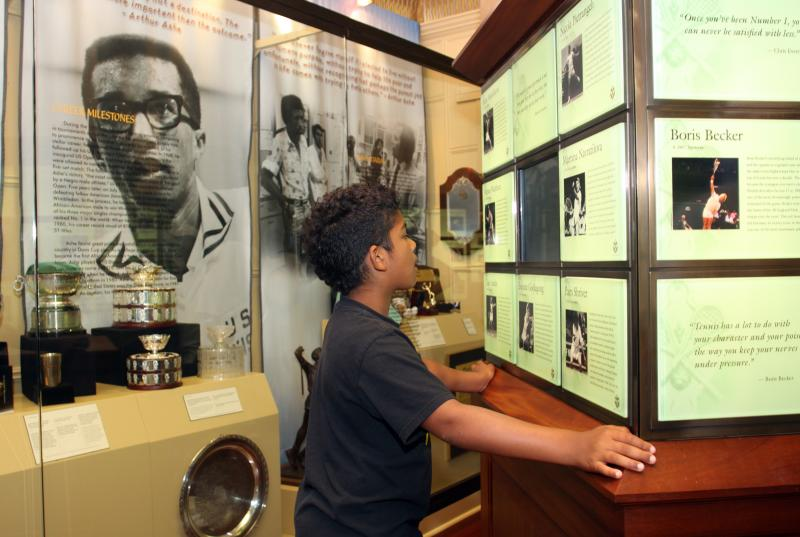 Child at Kiosk with Arthur Ashe in background