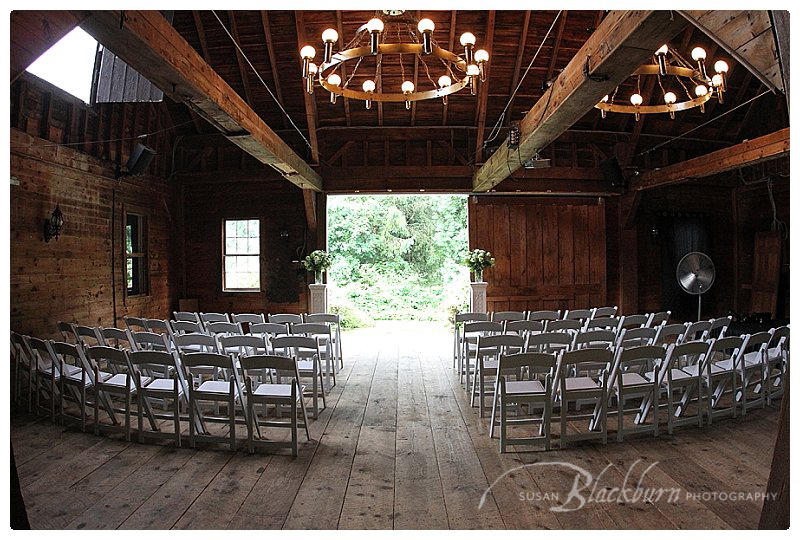 Barn set up for wedding with white chairs