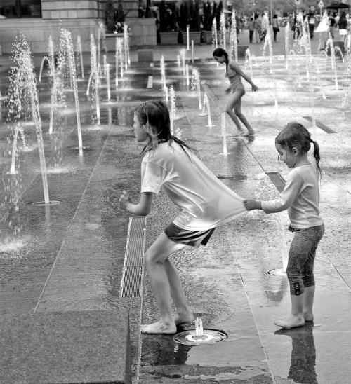 Black and white photo of three girls playing in fountain