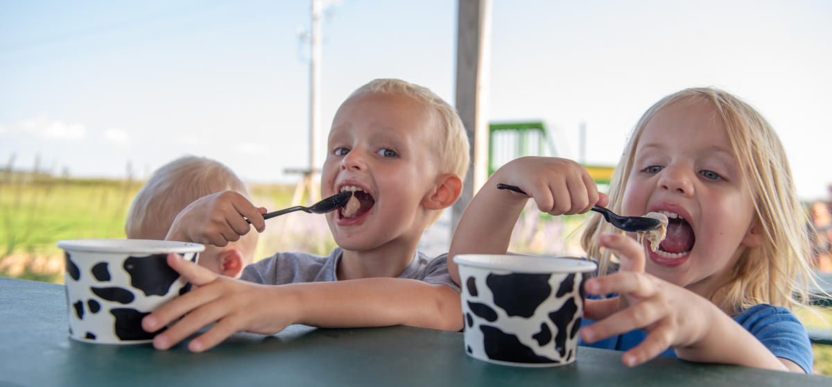 Two young children enjoy ice cream during the Meet the Sassy Cows experience