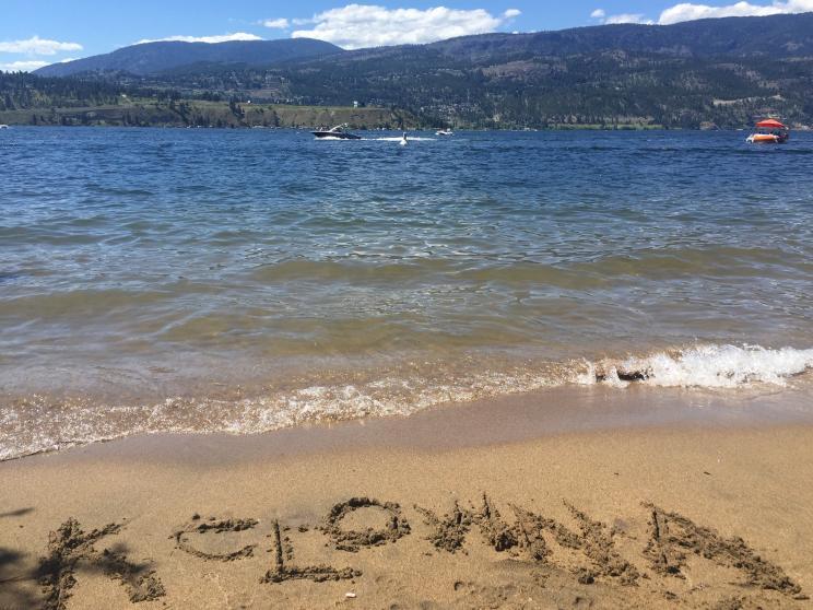 """Kelowna"" written in the sand on the shores of Okanagan Lake"