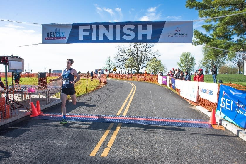 First-place winner Trevor van Ackeren of Bethlehem blasts across the finish line to complete the 2017 Valley Forge Revolutionary 5-Mile Run®. He completed the course in 25:28.